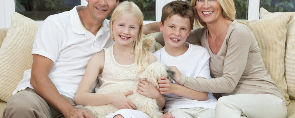 An attractive happy family of mother, father, son and daughter sitting on a sofa at home having fun with pet dog