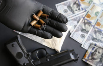Gun lying on the table. Man in black gloves holding bullets. Illegal drug selling. Criminal problems. Dollars.